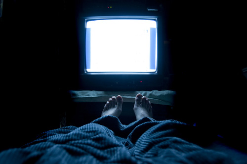 feet poking out from blanket in front of glowing TV set